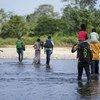 Romeu et Kulutwe et leurs familles, originaires d'Angola, traversent la rivière Tuquesa vers Bajo Chiquito, le premier village au Panama à la frontière avec la Colombie.