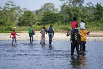 Los hermanos angoleños Romeu y Kulutwe y sus familias cruzan el río Tuquesa hacia el Bajo Chiquito, el primer pueblo panameño en la frontera con Colombia.