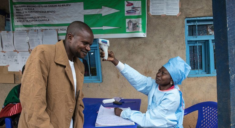 A medical practitioner measures the temperature of a local resident by infrared thermometer.