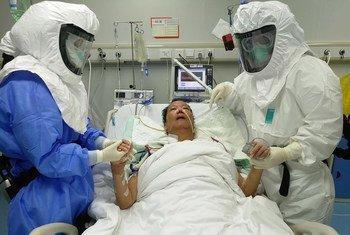 Trabajadores de salud en China atendiendo a un paciente.