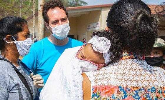 Uma funcionária do Unicef conversa com mulheres em um centro de saúde localizado nos arredores de Caracas, Venezuela.