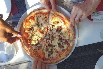 أصدقاء يزورون كرواتيا، ويتشاركون في تناول البيتزا وهو ما يشير إلى أهمية السلامة الغذائية للسياحة والازدهار الاقتصادي.
