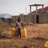طفلة تحمل صفائح مياه فاغة لتملأها من صنبور قريب يوفر مياه غير معالجة من نهر النيل في جوبا، جنوب السودان.
