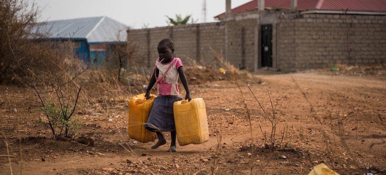 Uma criança carrega recipientes vazios para encher com água de uma torneira próxima, que fornece água não tratada do rio Nilo em Juba, Sudão do Sul