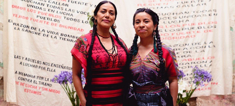La cantante mexicana Lila Downs (derecha) y la cantautora guatemalteca Sara Curruchich con la letra de la canción Pueblos en el telón de atrás.