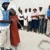 Bibi anasaidiwa kutembea ili afike kwenye kibanda cha kupiga kura mnamo 2006, huko Port-au-Prince, na afisa wa polisi wa Umoja wa Mataifa.