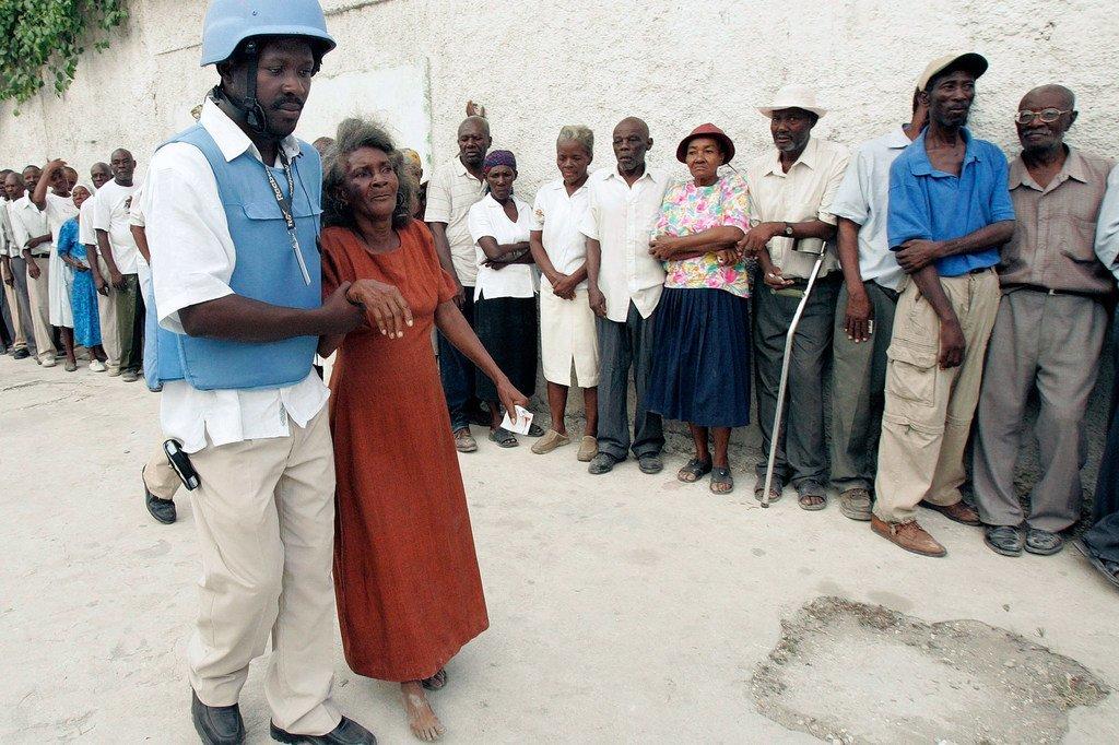 Un officier de police des Nations Unies aide une femme âgée à se rendre à l'isoloir dans la capitale haïtienne Port-au-Prince (archive)