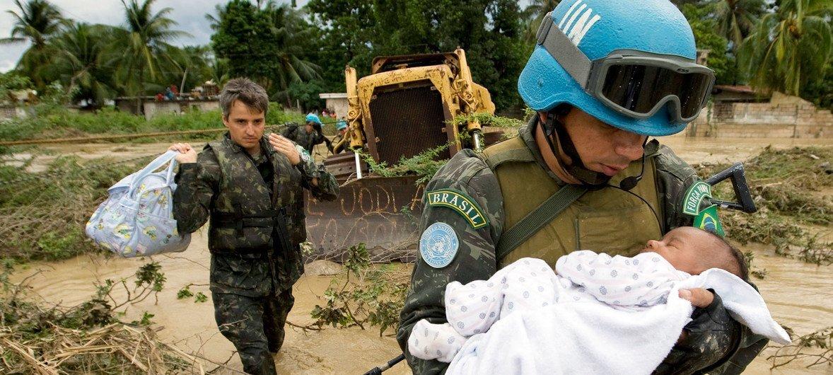 Un miembro brasileño de las fuerzas de mantenimiento de la paz de las Naciones Unidas rescata a un niño después de que partes de la capital de Haití, Puerto Príncipe, se inundaran durante una tormenta tropical en 2007.