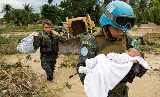 Boina-azul do Brasil salva criança após inundações causadas por uma tempestade tropical em 2007 em Porto Príncipe.