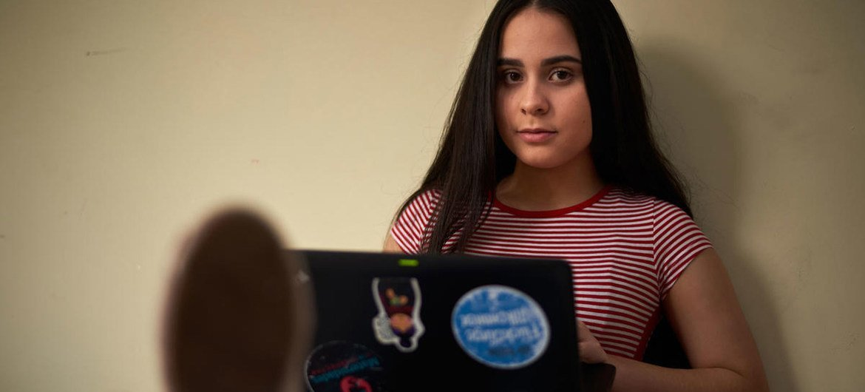 La estudiante refugiada venezolana Emily usa su computadora portátil en Quito, Ecuador.
