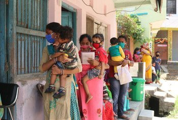 Parents and caregivers line up with their children at an immunization centre in Janakpur, southern Nepal.