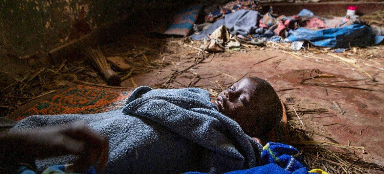 Пятилетняя девочка спит на кирпичном полу в здании колониальной эпохи, где нашли приют перемещенные семьи в лагере Изинга в Боге, ДР Конго