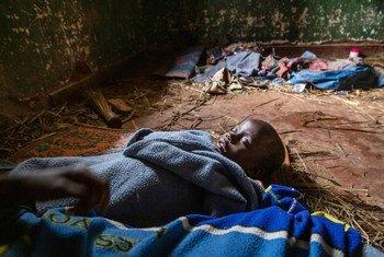 Mtoto wa miaka mitano akiwa amelala sakafuni kwenye jengo la enzi za kikoloni linalowahifashi wakimbizi kambi ya Izinga Boga, DRC