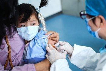 Una niña de 3 años recibe una vacuna en un centro de salud comunitario en Beijing, China.