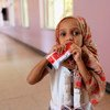 A small girl eats a peanut-based paste while being treated for malnutrition at a hostpial in Sa'ana, Yemen.