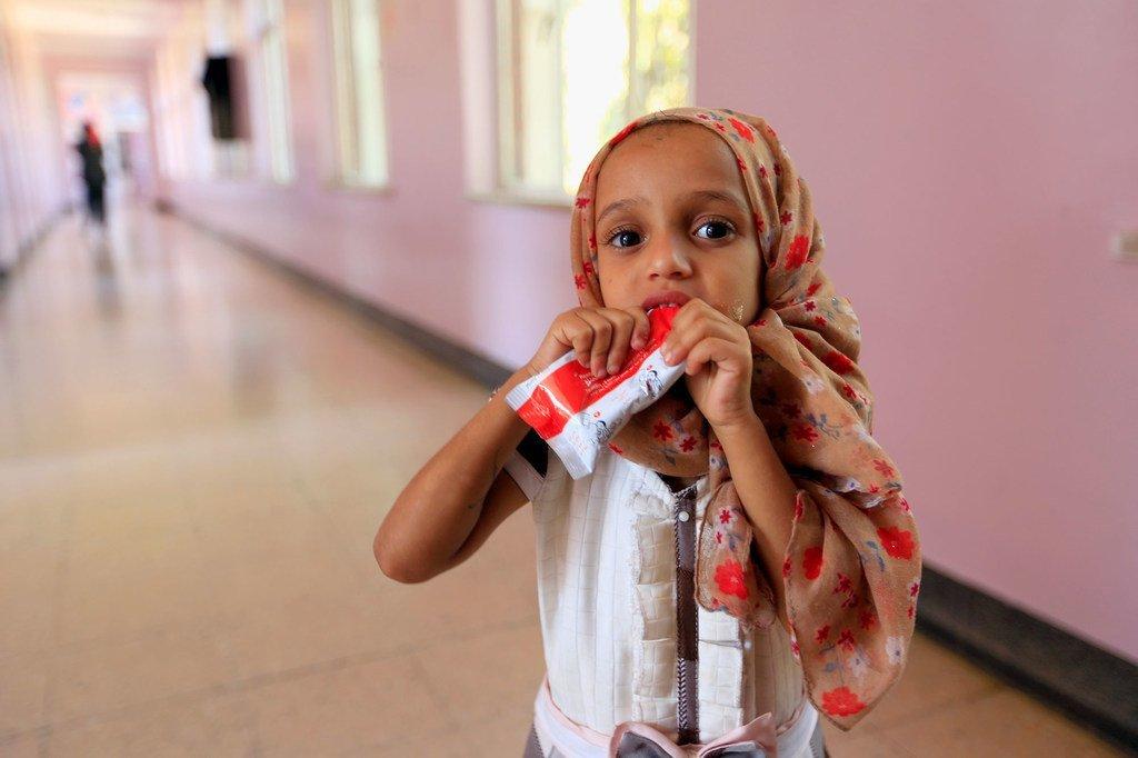 Une petite fille mange une pâte à base d'arachide alors qu'elle est soignée pour malnutrition dans un hôpital à Sa'ana, au Yémen.