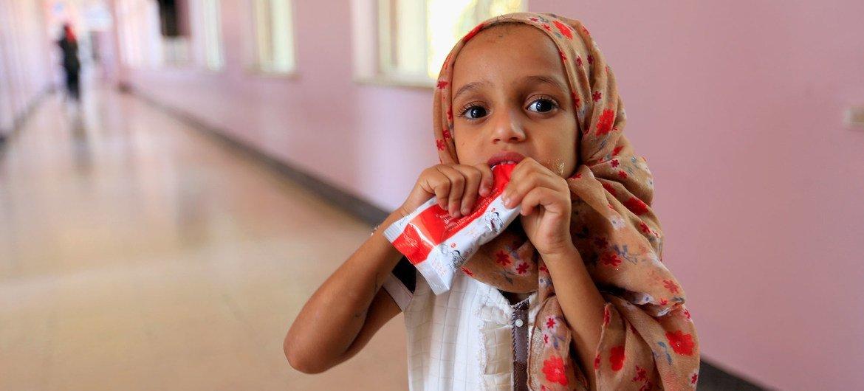 فتاة صغيرة تتناول عجينة الفول السوداني أثناء علاجها من سوء التغذية في مستشفى في صنعاء، اليمن.