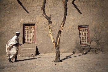 أحد السكان يسير قرب مسجد دجينغاربير في تمبكتو بمالي، وقد كانت مدينة أسطورية معروفة بمجموعة من المخطوطات الثمنية، وهي الآن على لائحة اليونسكو للمواقع الأثرية المهددة.