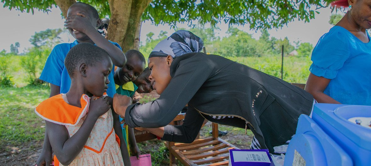 Uma profissional de saúde se prepara para imunizar uma jovem em uma escola primária no distrito de Busia, no Uganda.