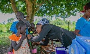 عاملة صحية تقوم بتطعيم فتاة صغيرة في مدرسة ابتدائية في منطقة بوسيا، أوغندا.