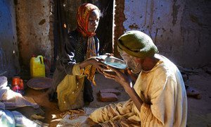 A seven-year-old girl gives water to her grandfather while he prays in a camp for internally displaced people in Darfur, Sudan.