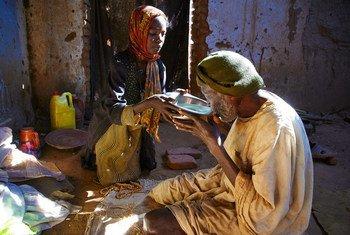 Binti wa miaka 7 akimpa maji ya kunywa bibi yake kwenye kambi ya wakimbizi wa ndani Darfur nchini Sudan