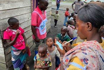 Uma profissional de saúde da República Democrática do Congo com crianças que esperam para receber a vacinação contra o sarampo.