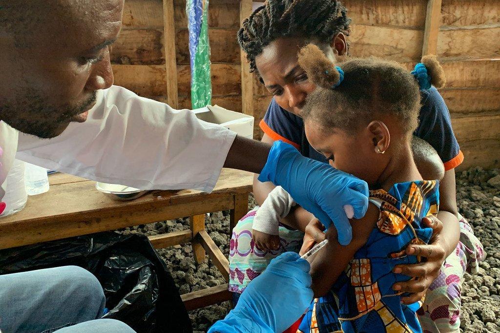 Un professionel de santé vaccine une fillette contre la rougeole en République démocratique du Congo.