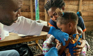 A health worker administers a vaccination against measles on a young girl in the Democratic Republic of the Congo.