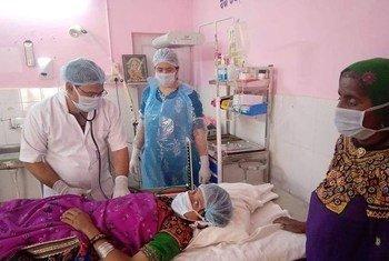 Trabajadoras de primera línea dan servicios de salud reproductiva a una mujer durante la pandemia.