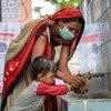 भारत के गुजरात में स्वच्छता और कोविड महामारी की रोकथाम के लिये एक सामुदायिक स्वास्थ्य कार्यकर्ता, एक बच्चे को सही ढंग से हाथ धोना सिखाते हुए.