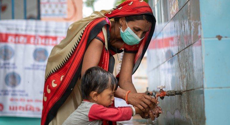 गुजरात में स्वच्छता और कोविड महामारी की रोकथाम के लिये एक सामुदायिक स्वास्थ्य कार्यकर्ता एक बच्चे को सही ढंग से हाथ धोना सिखा रहा है.
