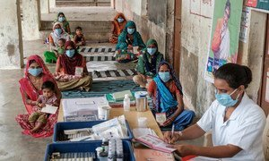 Families receive vaccinations and counselling at a socially distanced Village Health and Nutrition Day in Gujarat, India.