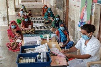 在印度古吉拉特邦的一个村庄,人们在健康和营养日接受疫苗注射和咨询。