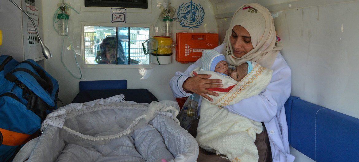 A health care worker carries the twins before they board the medical evacuation flight to Amman, Jordan.