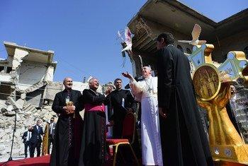 Le Pape François (au centre) libère une colombe représentant la paix sur les ruines de l'Église syriaque catholique de l'Immaculée Conception à Mossoul, en Iraq.