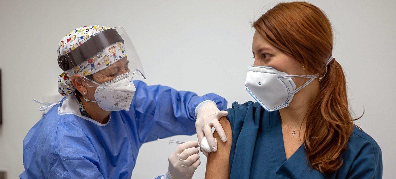 Una sanitaria pone la primera dosis de la vacuna contra el COVID-19 a una paciente en Colombia.