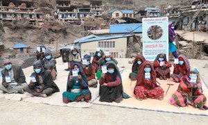 Les personnes âgées d'un village reculé du Népal brandissent leur carte de vaccination après avoir reçu des vaccins contre la Covid-19.