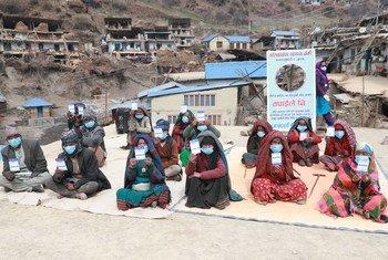 नेपाल के एक गाँव में कोविड-19 वैक्सीन लगवाने के बाद अपने टीकाकरण कार्ड को दिखाते वृद्धजन.