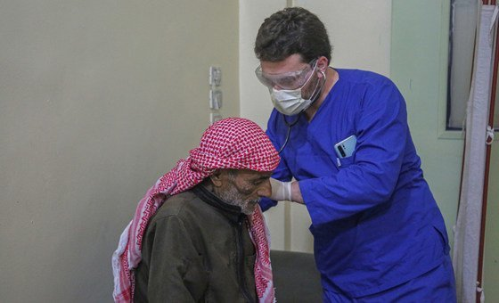 A doctor checks a patient displaced by conflict in Syria.