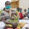Requerente de asilo na República Democrática do Congo com seus filhos depois de atravessar a fronteira para Uganda