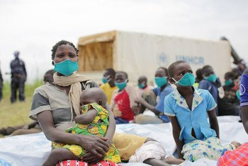 Une demandeuse d'asile de 29 ans, originaire de la République démocratique du Congo, est assise avec ses enfants après avoir subi un examen médical près du poste frontière de Zombo, en Ouganda.