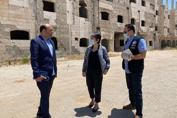 Глава Представительства ВОЗ в Сирии Акджемал Магтымова (в центре) у разрушенного здания больницы в г. Хомс.
