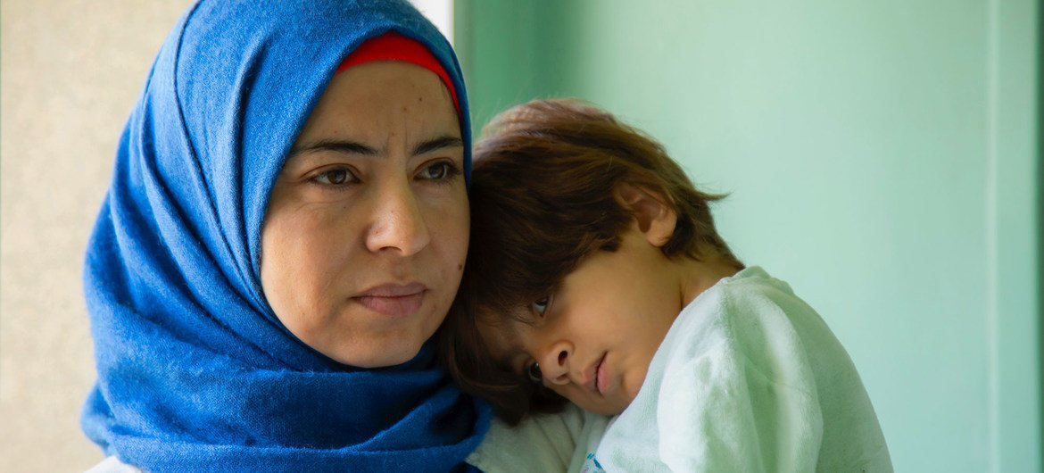 A mother caught up in Syria's long-running conflict, holds her child.