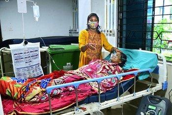 Mgonjwa wa ugonjwa wa COVID-19 akihudumiwa na mwanae wa kike katika hospitali jimbo la Bengal magharibi, India.