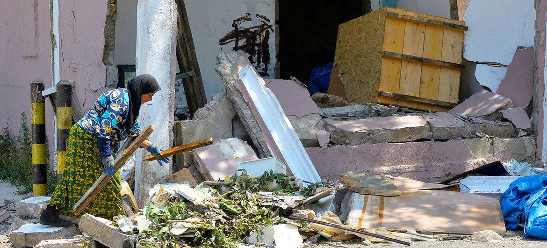 在8月4日爆炸中,这名贝鲁特妇女的房屋被炸毁。她正在瓦砾中搜寻残存的物品。