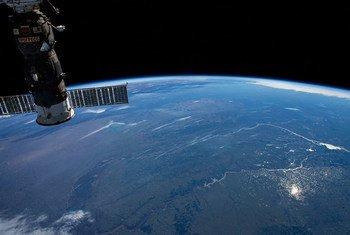 قمر صناعي، كما نشاهده من الفضاء، يسير فوق أمريكا الجنوبية.
