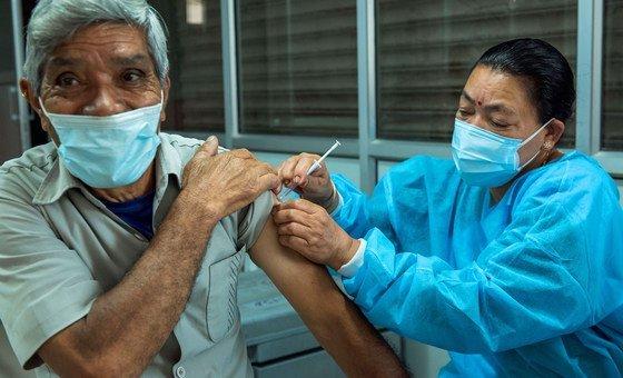 नेपाल में एक वृद्धजन को कोरोनावायरस वैक्सीन की दूसरी ख़ुराक दी जा रही है.