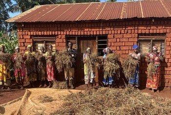 Wakulima waliopokea mafunzo kutoka kwa FAO wakiwa wameshika zao la mikunde.