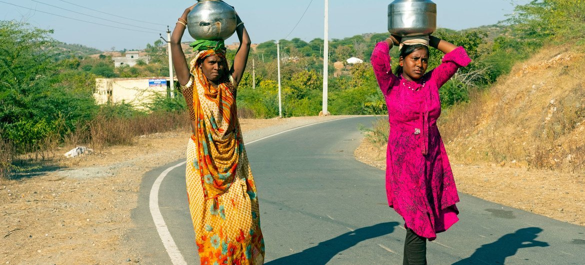A 15-year-old girl in India carries water (right) as she is forced to miss school because she lacks the technology attend online classes.